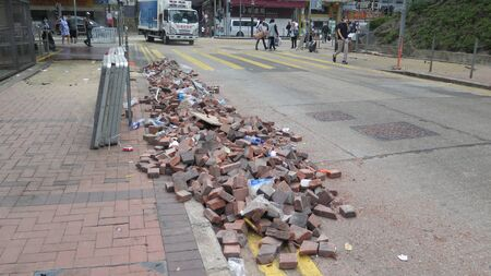 Hong Kong, East Asia - November 20, 2019: People walking on torn up pavement after student demonstration
