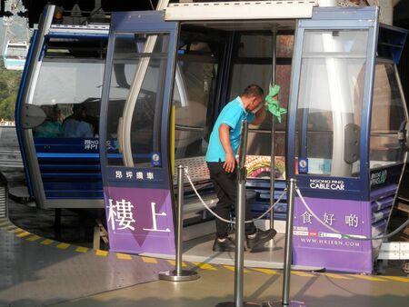 Hong Kong Lantau Island - November 18, 2019: Man cleaning cable car pod on the move at top station of Ndong Ping village