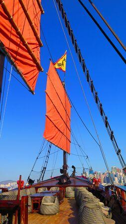 Hong Kong, East Asia - November 22, 2019: Red sail of the AquaLuna touring junk boat in Victoria harbor, Hong Kong