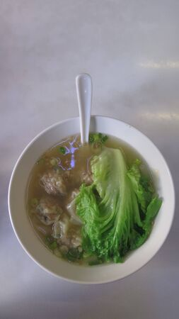 Bowl of wonton soup with cabbage and dumplings served for breakfast in Kowloon restaurant, Hong Kong Stockfoto
