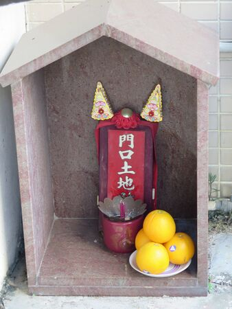 Small ornamental buddist shrine with incense sticks and fresh food offerings