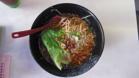 Bowl of bean and noodle soup with cabbage and dumplings served for breakfast in Kowloon restaurant, Hong Kong Redactioneel