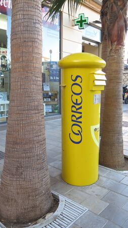 Yellow Spanish post box on pavement between two palm trees in Malaga, Spain