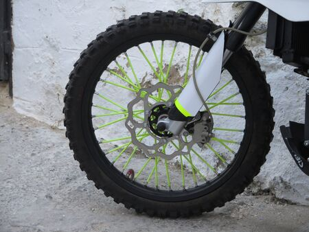 Closeup of front wheel of small motorbike in Spanish village street Stockfoto