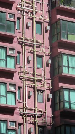 Downpipes and drain pipes on outside of tall building in Hong kong business districts