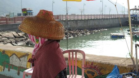 Chinese woman facing away from camera wearing traditional woven straw hat in Hong Kong fishing village Stock Photo