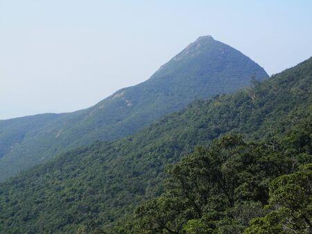 Wooded mountain peaks against blue sky viewed from Victoria Peak, Hong Kong Stock Photo
