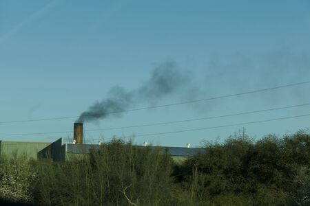 Factory chimney spewing out black smoke in Andalusian industrial park Reklamní fotografie