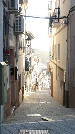 Looking down narrow steep street in Andalusian village in winter sunshine