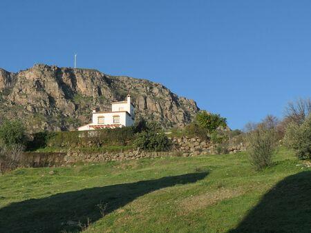Long shadow on grass below house nesting below large rock
