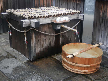 Kyoto, Japan -  November 30, 2019: Fresh drinking water provided through bamboo pole at sake brewery