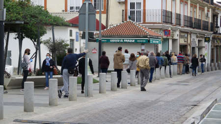 Alora, Spain - Apill 4, 2020: Large crowd outside bank on pension day respecting social distancing rules in Andalusian village