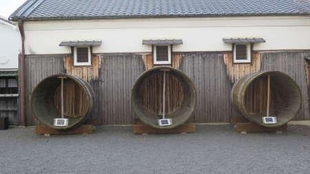 Kyoto, Japan - November 30, 2019: Large old wooden sake fermenting barrels brewery back yard