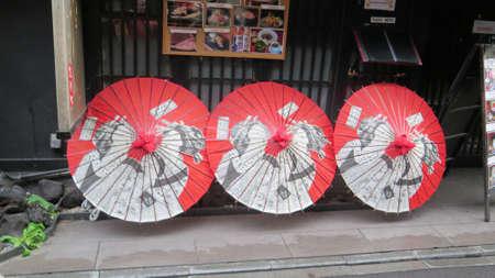 Kyoto, Japan - November 28, 2019: Three Japanese umbrellas on pavement in narrow Kyoto street, Japan