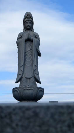 Kyoto, Japan -  December 1, 2019: Tall granite carved statue in Kyoto temple garden
