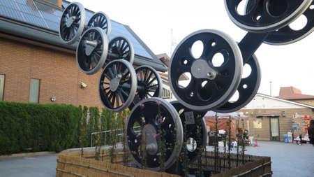 Large artful sculpture of train wheels in grounds of Sagano railway museum, Japan Editoriali