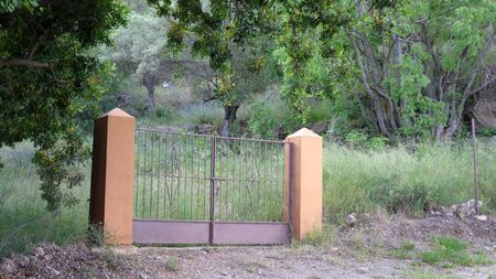 Painted Stone pillars and gate to rocky field in rural Andalusia Archivio Fotografico - 148409339