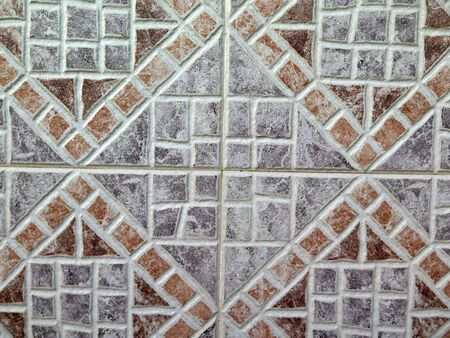 Closeup of dark brown and grey ceramic tiles on wall in village in Andalusia