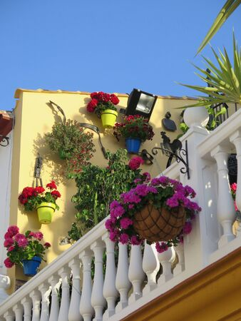 Hanging baskets on outdoor light against yellow painted wall on open terrace balcony in Andalusian village