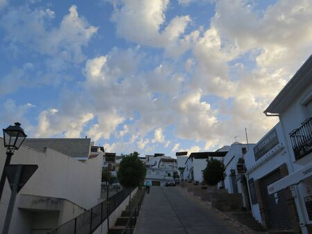 White clouds in early morning sunshine over steep village street