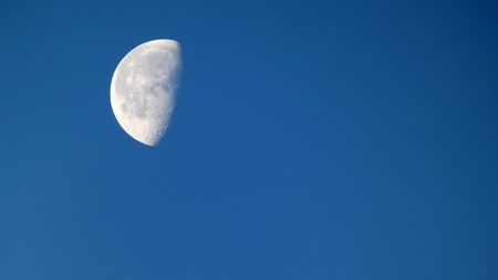 Daytime large waning moon in blue sky in rural Andalusia Archivio Fotografico