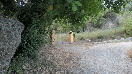 Painted Stone pillars and gate to rocky field in rural Andalusia