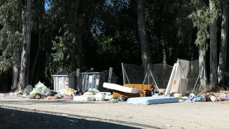 Household waste dumped next to overflowing containers in forrest layby