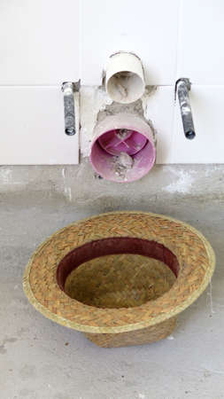 Laborers strawhat upside down below exposed lavatory pipes