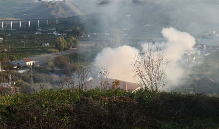 Farmer burning trimmings from fruit trees in fron of house in early morning Andalusian January sunshine