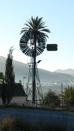 Tall palm tree and old water pump windmill in Andalusian village Archivio Fotografico