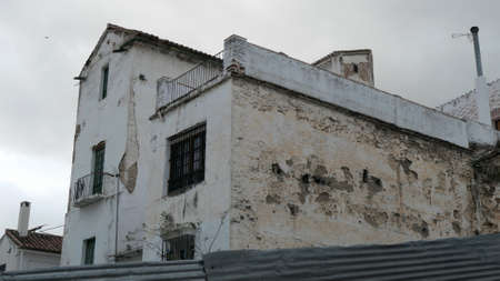 Damaged rough wall in narrow back street street in the Andalusian village of �lora