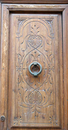 Hand carved wooden window shutter with decorative iron ring