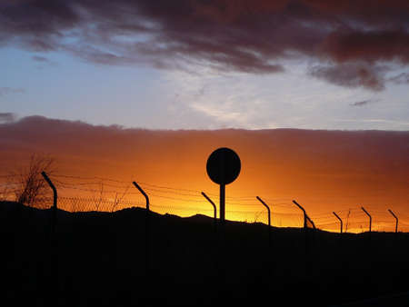 Dramatic golden red dawn silhouetting Fence and traffic sign in Andalusian countryside