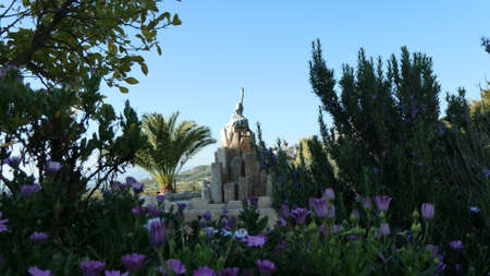 Focus on purple white daisies in front of guitar fountain in Andalusian village Archivio Fotografico