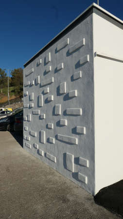 Brick wall with protruding squares and rectangles on village public convenience