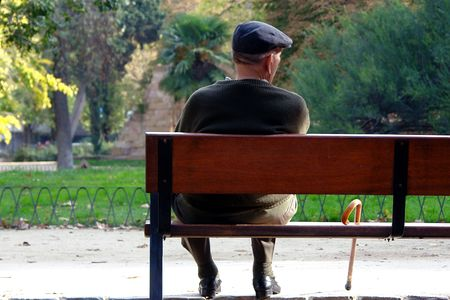 a cane: old man sitting on a park bench