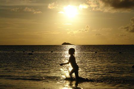 splashing child at sun set                               photo