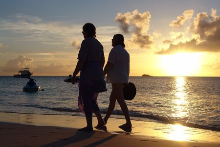 couple walking at sun set on a beach                            photo