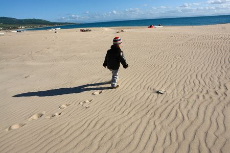 boy walking over pristine sand dunes                               photo