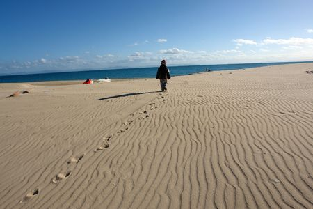 boy walking on a deserted beach                                photo