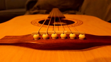 Camera focused on the pegs of a blonde-wood guitar. 版權商用圖片
