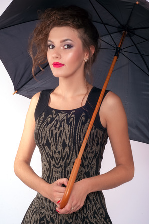 decollete: Made up woman holding black umbrella on white background in studio