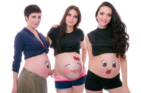 body art: Three pregnant women with body art isolated on white