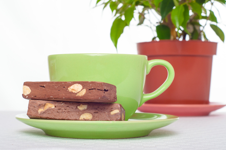 tucker: Cup of tea and sweets on books stack. Concept of reading, studying or resting at home. Stock Photo
