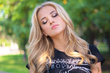 Young blond made up woman portrait. Girl with long hair closed her eyes in park.