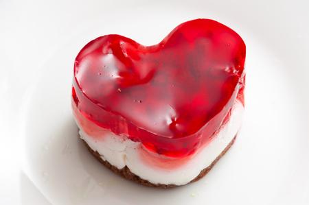 tucker: Fruit cake on plate. Tucker close up shot. Sweet stuff on white dish. Bake with strawberry.