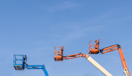 Three Cherry Picker machines against a blue sky