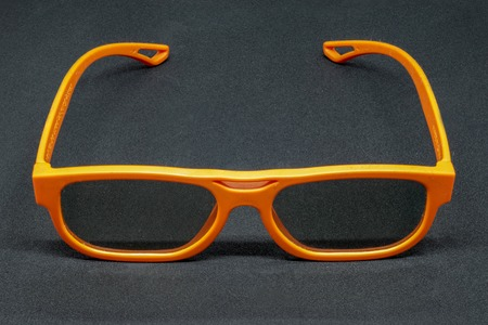 Orange 3 Dimensional glasses on a dark grey background Banco de Imagens