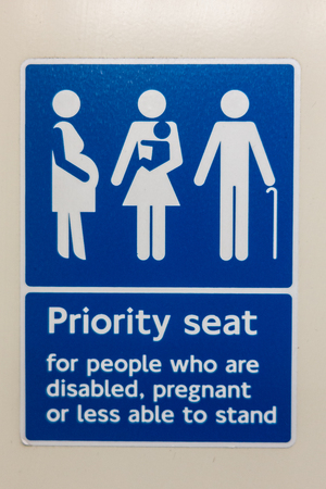Priority seat for people who are disabled, pregnant or less able to stand sign on a London train
