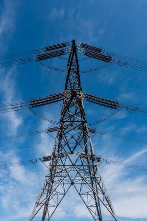 Single overhead line power pylon against a blue sky Stockfoto